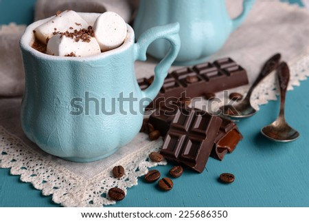 Cup of coffee with marshmallow and chocolate on wooden table - stock photo