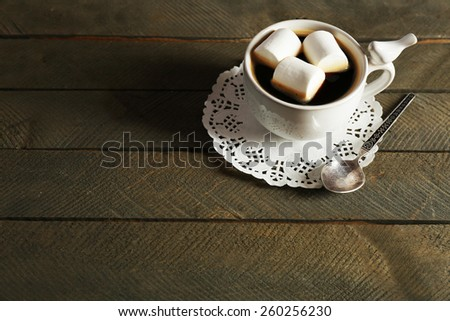 Cup of coffee with marshmallows on rustic wooden planks background - stock photo