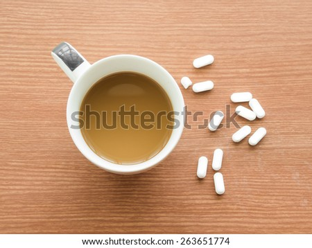Cup of coffee with medicine pills - stock photo