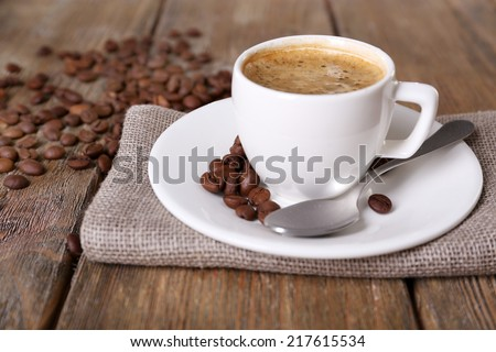 Cup of coffee with milk and coffee beans on napkin on wooden background - stock photo
