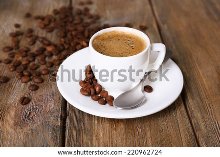 Cup of coffee with milk and coffee beans on wooden background - stock photo