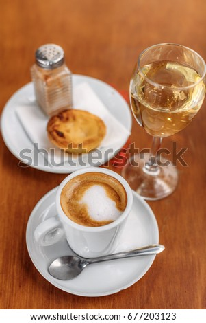 "Cup of coffee with milk (known as ""meia de leite""), accompanied by ""pastel de nata"" pastry and glass of white wine."