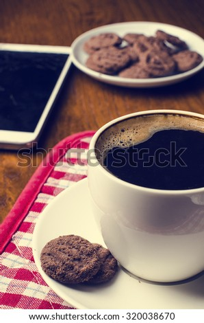 Cup of coffee with mobile phone and cookies on a wooden table