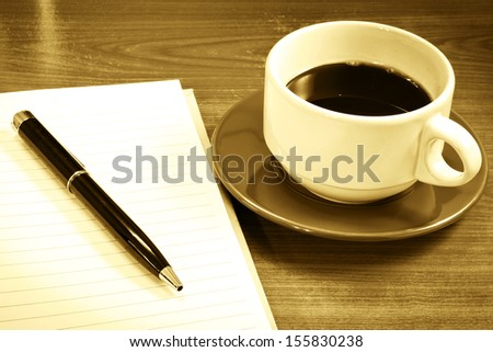 cup of coffee with notebook and pen - stock photo