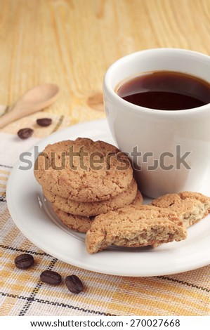 Cup of coffee with oatmeal cookies on wooden table - stock photo