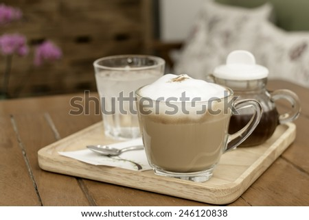 Cup of coffee with on wood table in the living room made with vintage tones - stock photo