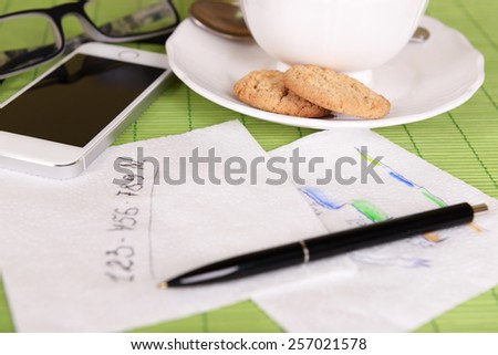Cup of coffee with pen and business notes on napkin on green bamboo mat background - stock photo