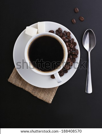 cup of coffee with pile of beans - stock photo