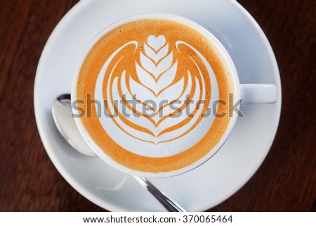 Cup of coffee with professional latte-art on wooden table. Shalow dof. - stock photo