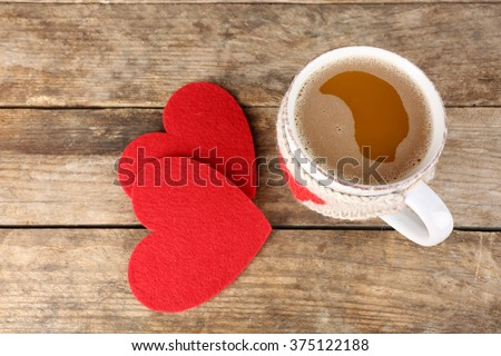 Cup of coffee with red felt hearts on wooden background, close up - stock photo