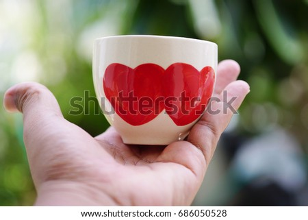 Cup of coffee with red heart in hand on blur green background