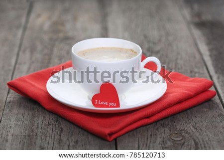 Cup of coffee with red heart on wood background
