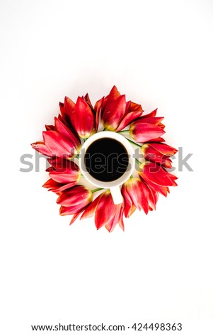 Cup of coffee with red tulip flower buds. Flat lay, top view