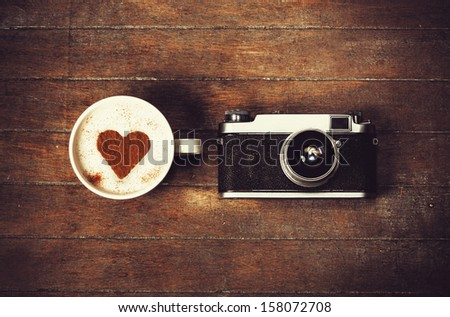 Cup of coffee with retro camera - stock photo