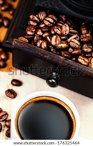 Cup of coffee with roasted coffee beans macro. Black coffee in a white cup on a napkin close up.