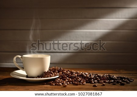 Cup of coffee with smoke and coffee beans on wooden background.This image with no smoke is available