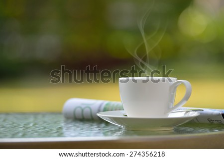 Cup of coffee with smoke and newspaper in garden