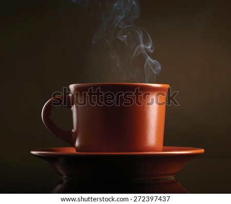 Cup of coffee with smoke over dark background