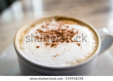 Cup of coffee with soft microfoam and cinnamon ground on marble table