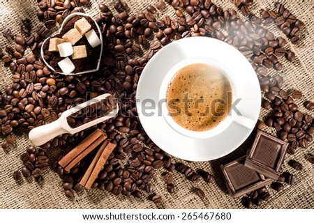 Cup of coffee with steam, coffee beans, chocolate pieces, cinnamon sticks, white and brown sugar, and scoop on burlap background. - stock photo