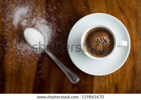 Cup of coffee with sugar on wooden table - stock photo