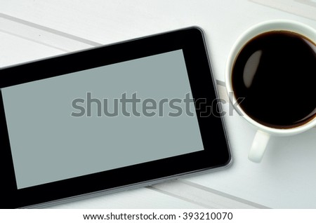 Cup of coffee with tablet pc on wooden table