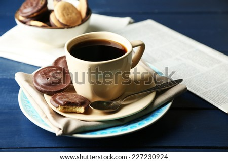 Cup of coffee with tasty cookies on color wooden background - stock photo