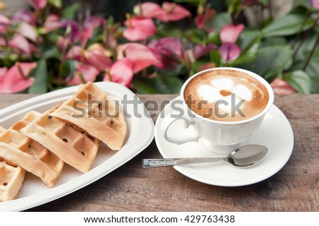 Cup of coffee with waffle on a wooden table