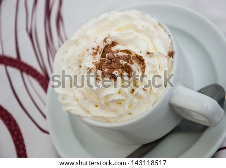 Cup of coffee with whipped cream on vintage tablecloth. Selective focus.