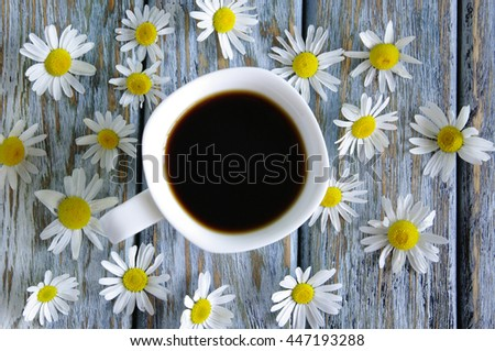 Cup of coffee with wild flowers