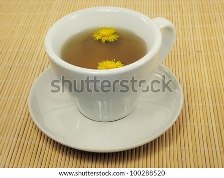 cup of colts Foot tea cup on a bamboo trivet - stock photo