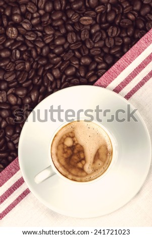 cup of creamy expresso over roasted coffee beans
