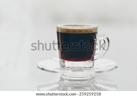 Cup of delicious freshly brewed full roast frothy black espresso coffee served in a glass mug and saucer on a reflective grey background - stock photo