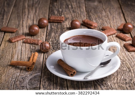 Cup of delicious hot chocolate with cinnamon and chocolate candies. - stock photo