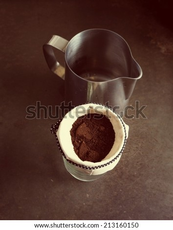 Cup of Dripping fresh hot coffee, blended coffee ground on paper filter, vintage color