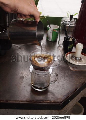 Cup of Dripping fresh hot coffee, pouring hot water to blended coffee on paper filter - stock photo