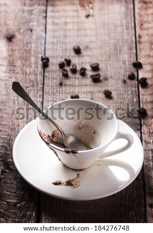 Cup of drunk coffee with coffee ground on old wooden table with coffee beans - stock photo