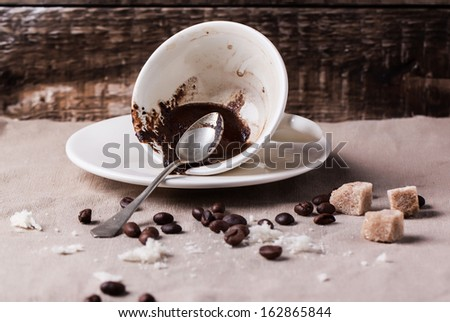 Cup of drunk coffee with coffee ground on table with crumbs and coffee beans - stock photo
