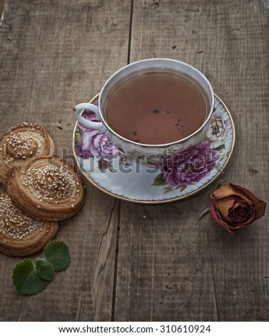 Cup of english tea, homemade bakery, puff cookies with sesame seeds on plate and dry rose - stock photo