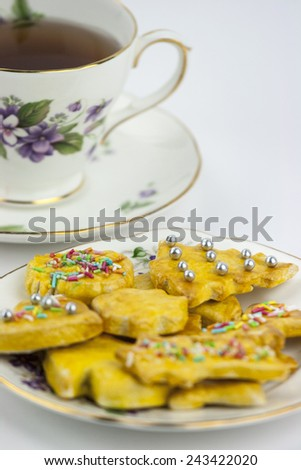Cup of english tea whit sweet and decored cookies - stock photo