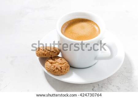 cup of espresso and almond cookies on a white table, horizontal