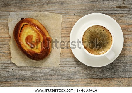 cup of espresso and bun on wooden background  - stock photo