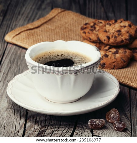 Cup of espresso and chocolate chip cookies, old wooden background