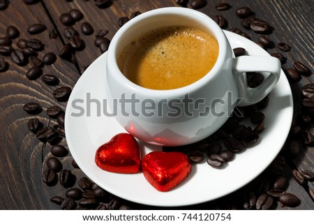 cup of espresso and chocolate sweets in the form of a heart on dark table, closeup