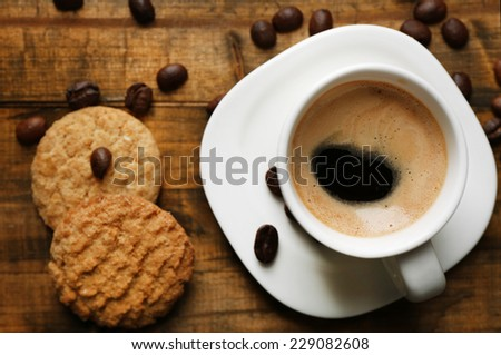 Cup of espresso and tasty cookie on wooden background - stock photo