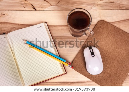 cup of espresso, checkered notebook and bun on wooden background - stock photo