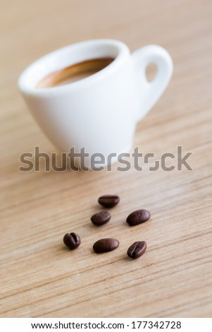 Cup of espresso coffee with coffee beans on the table, Artistic selective focus - stock photo