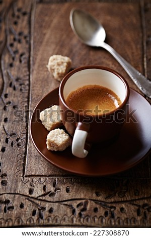 Cup of espresso with brown sugar cubes