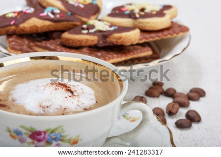 Cup of espresso with coffee beans and sweets on linen tablecloth. Focus on cup.