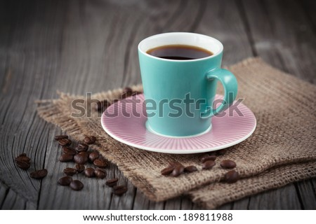 Cup of espresso with coffee beans on dark wooden background, selective focus - stock photo
